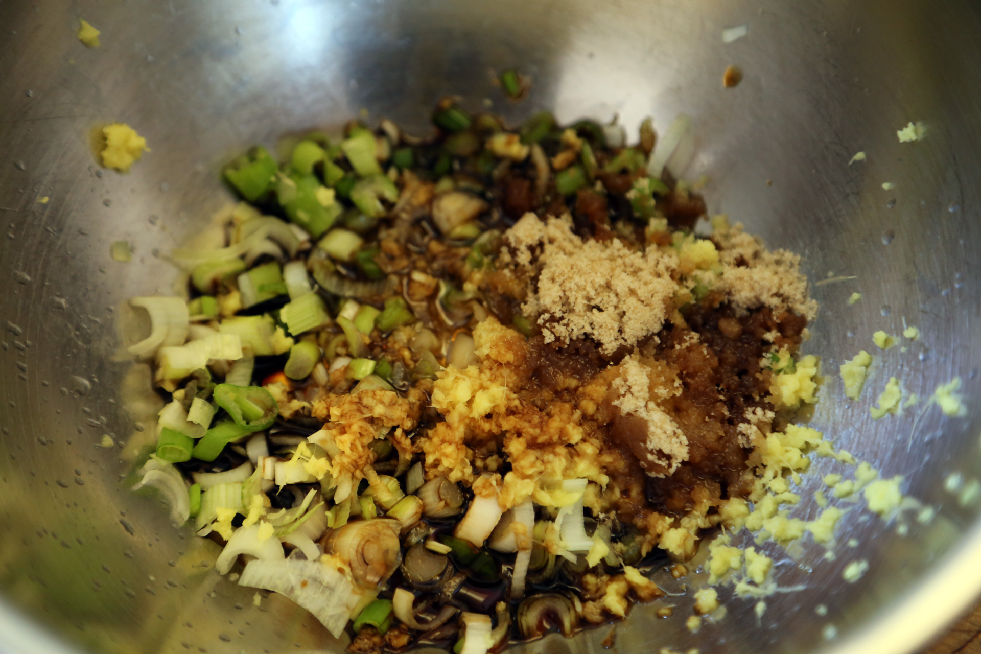 In a bowl, whisk together the green onions, soy sauce, sesame oil, sugar, and ginger.