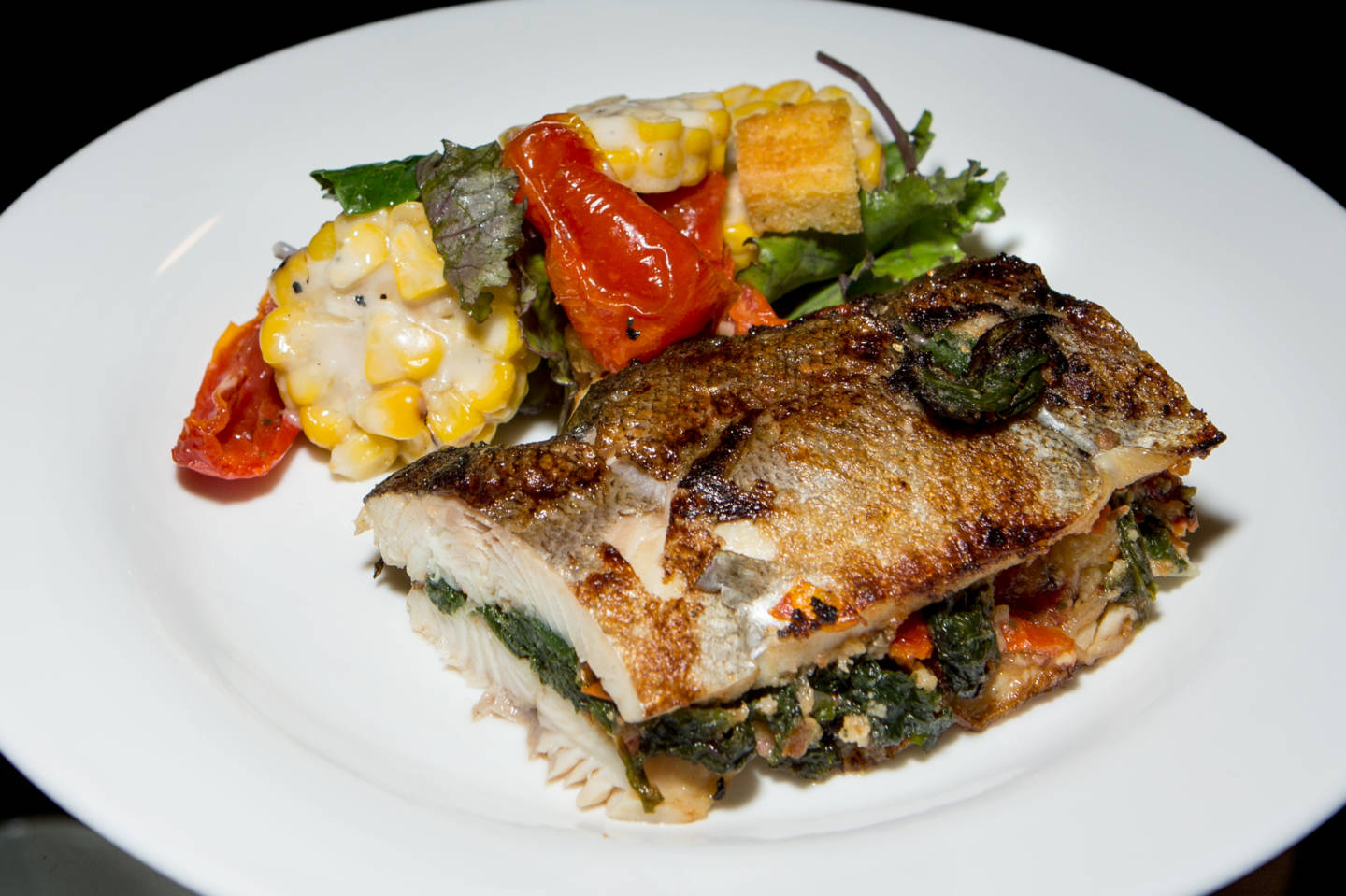 Pan Roast Rainbow Trout, served with cornbread and mustard greens stuffing and hazelnut brown butter, a seafood offering in the Western Range.  Ariel Zambelich/NPR