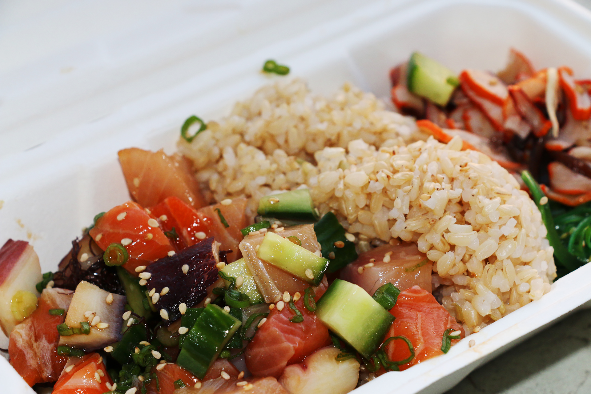 A bowl with salmon, octopus and hamachi on brown rice