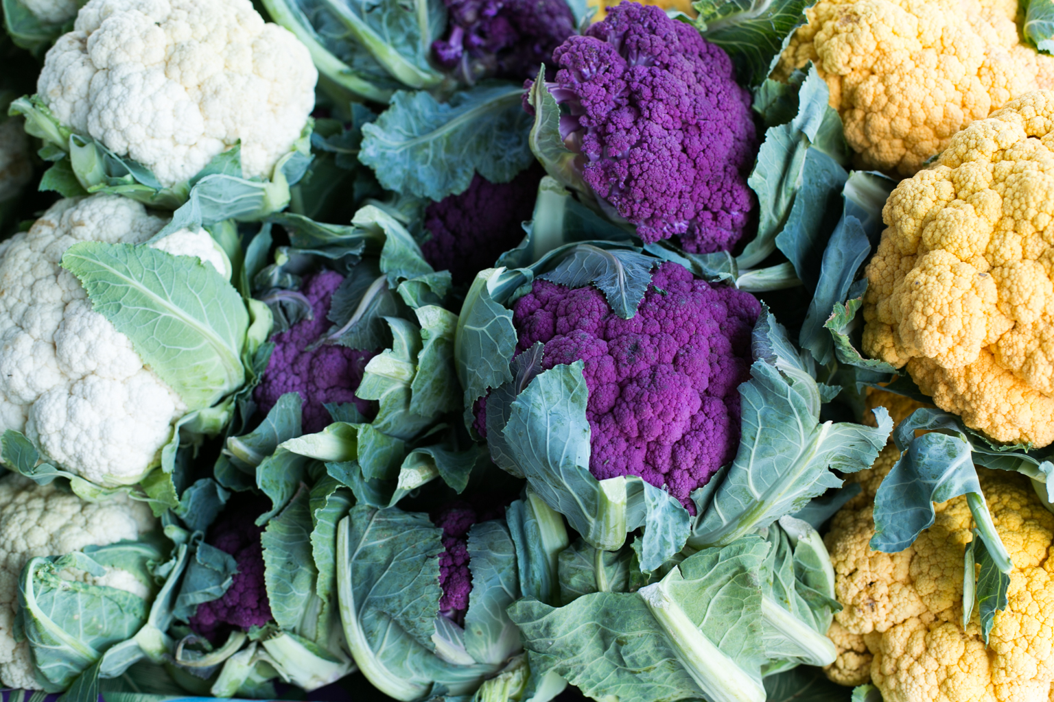 A rainbow of cauliflower for sale at the market.