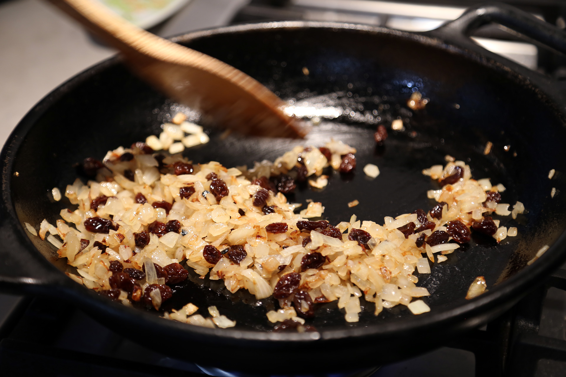 Add the raisins and garlic and fry until the raisins begin to puff and the garlic becomes fragrant, about 2 minutes.
