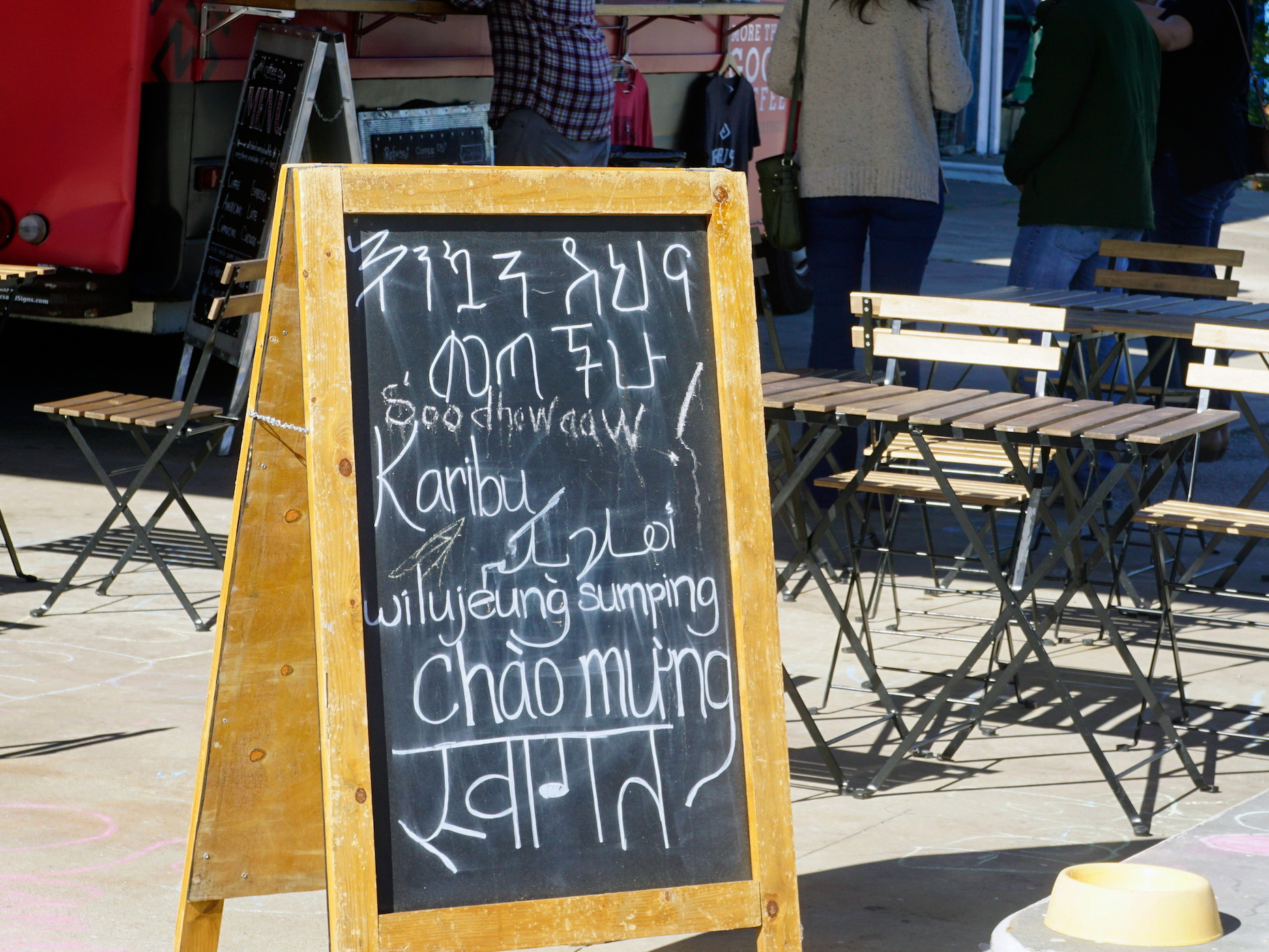 "A sign outside the Refuge Coffee food truck says ""Welcome"" in (top to bottom) Amharic, Somali, Swahili, Arabic, Sudanese, Vietnamese and Nepali."
