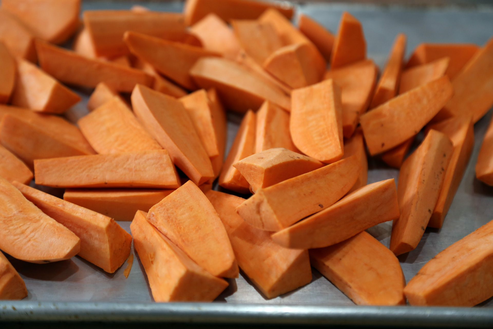 Cut the yams in half crosswise, then cut into equal-sized wedges, each about 1 by 3 inches.