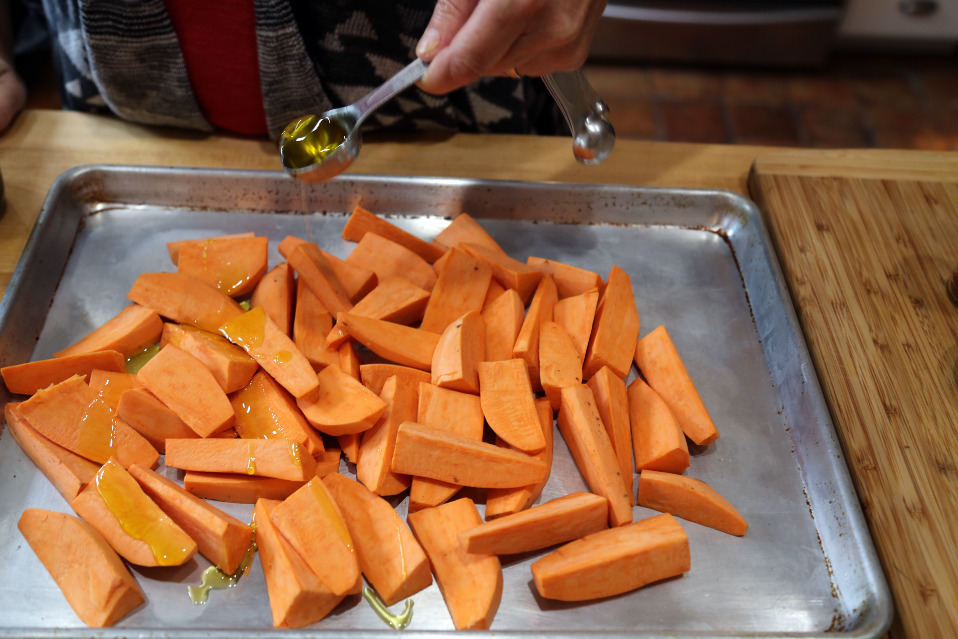 Add the yams to a large rimmed baking sheet and drizzle with the olive oil.