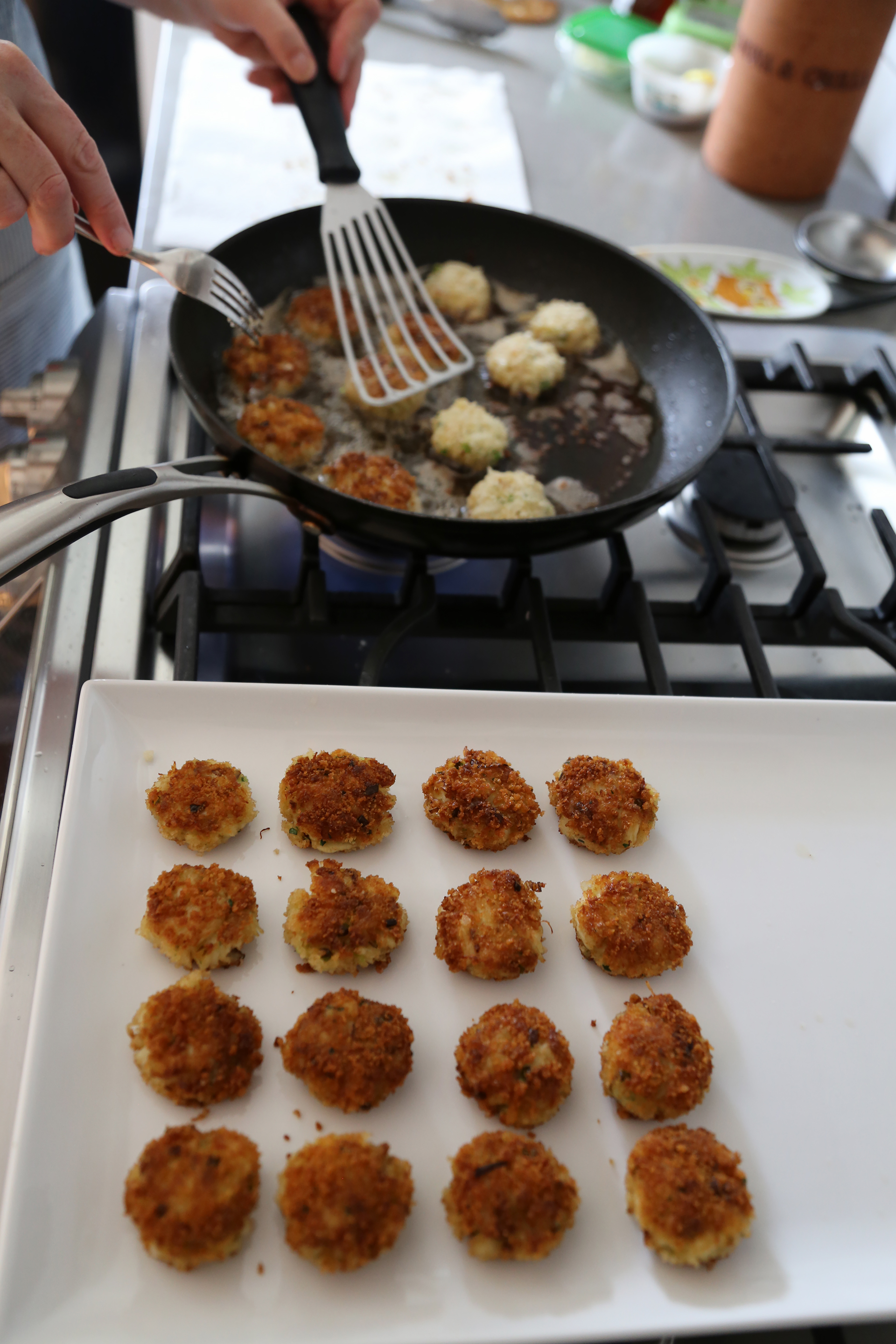 Transfer drained crab cakes to a platter and then fry the other half.
