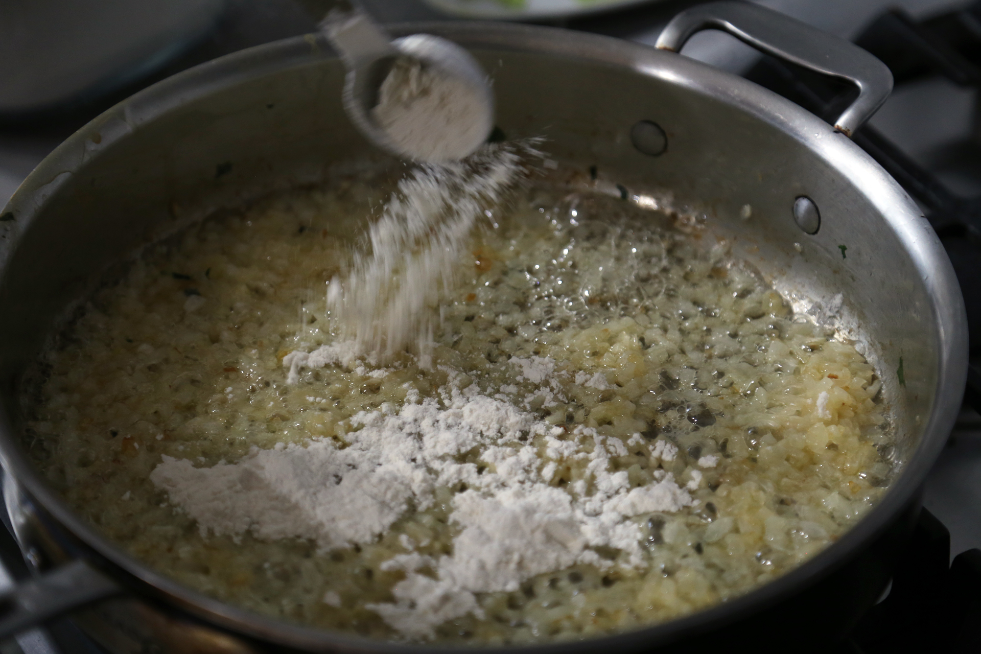 In the same pan, melt the remaining 5 tablespoons butter over medium heat. Add the onion and a sprinkle of salt and cook, stirring, until golden brown, about 10 minutes. Stir in the flour and let bubble for about 2 minutes.