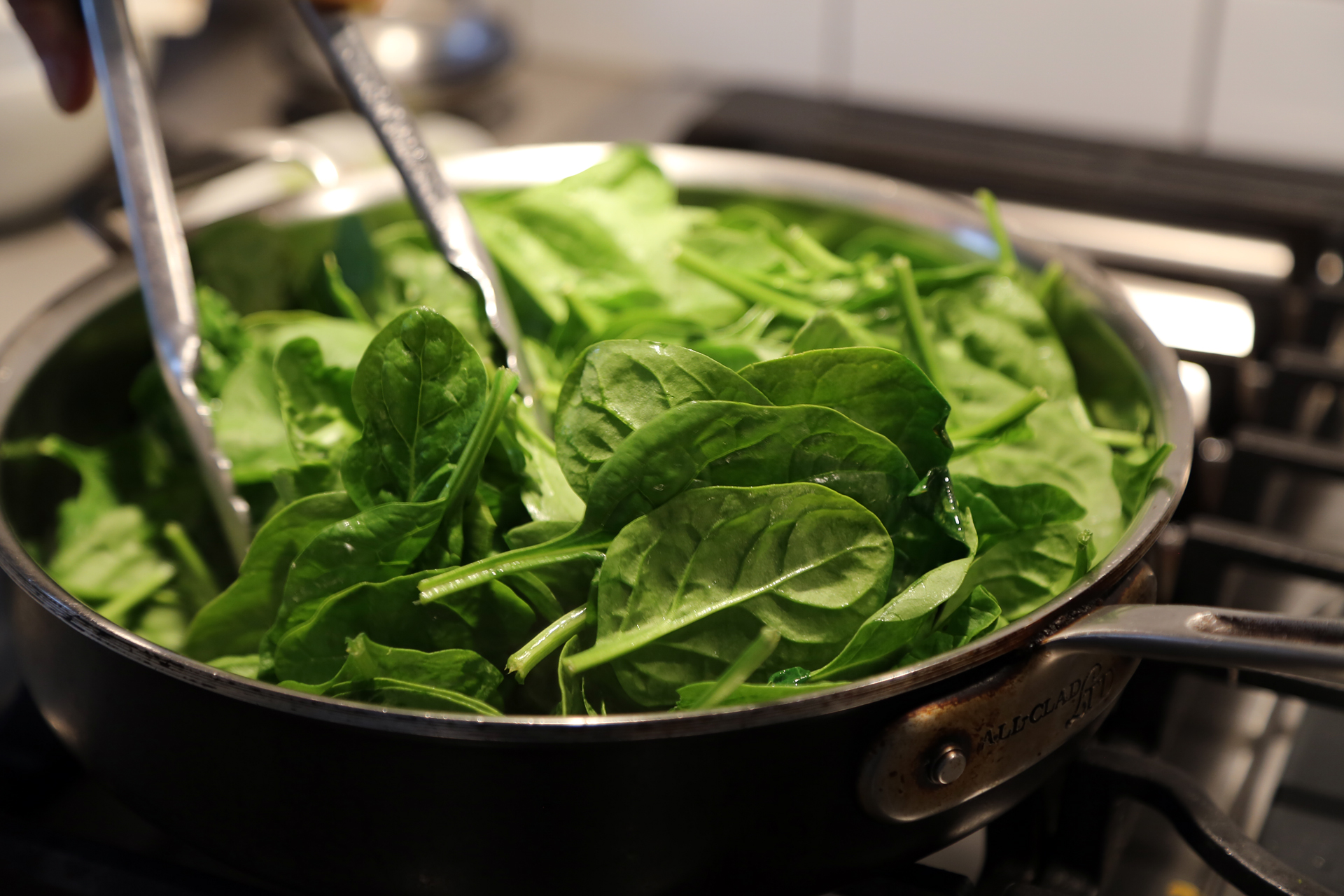 In a large frying pan or sauté pan over medium heat, melt 1/2 tablespoon of the butter. Add the spinach and cook, stirring often, just until barely wilted.
