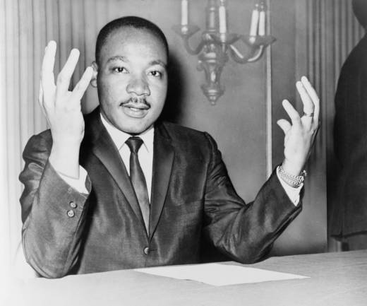 Rev. Martin Luther King, head-and-shoulders portrait, seated, facing front, hands extended upward, during a press conference