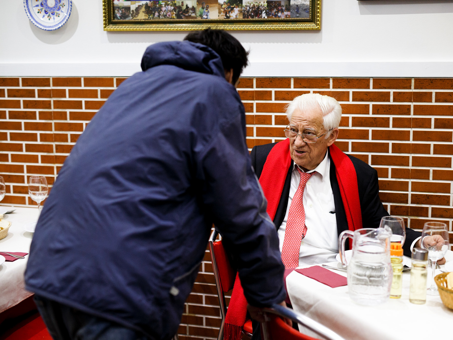 """A dinner patron chats with Father Angel (right), who says that he wants homeless people to """"eat with the same dignity as any other customer."""""""