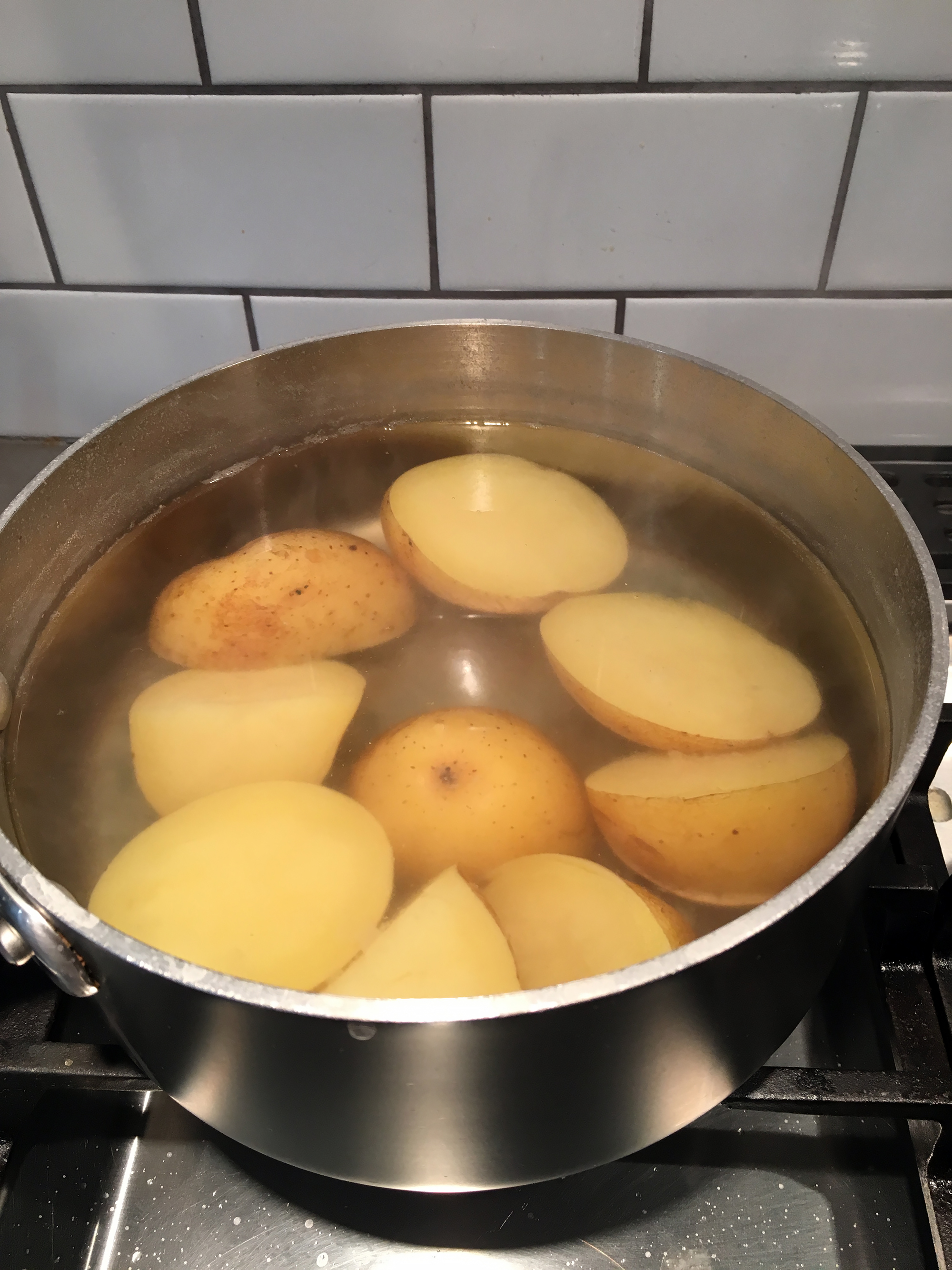 Put the potatoes in a saucepan with cold water to cover, add a few teaspoons kosher salt, then bring to a boil over medium-high heat. Reduce the heat to medium-low to maintain a simmer and cook until tender, about 20 minutes.