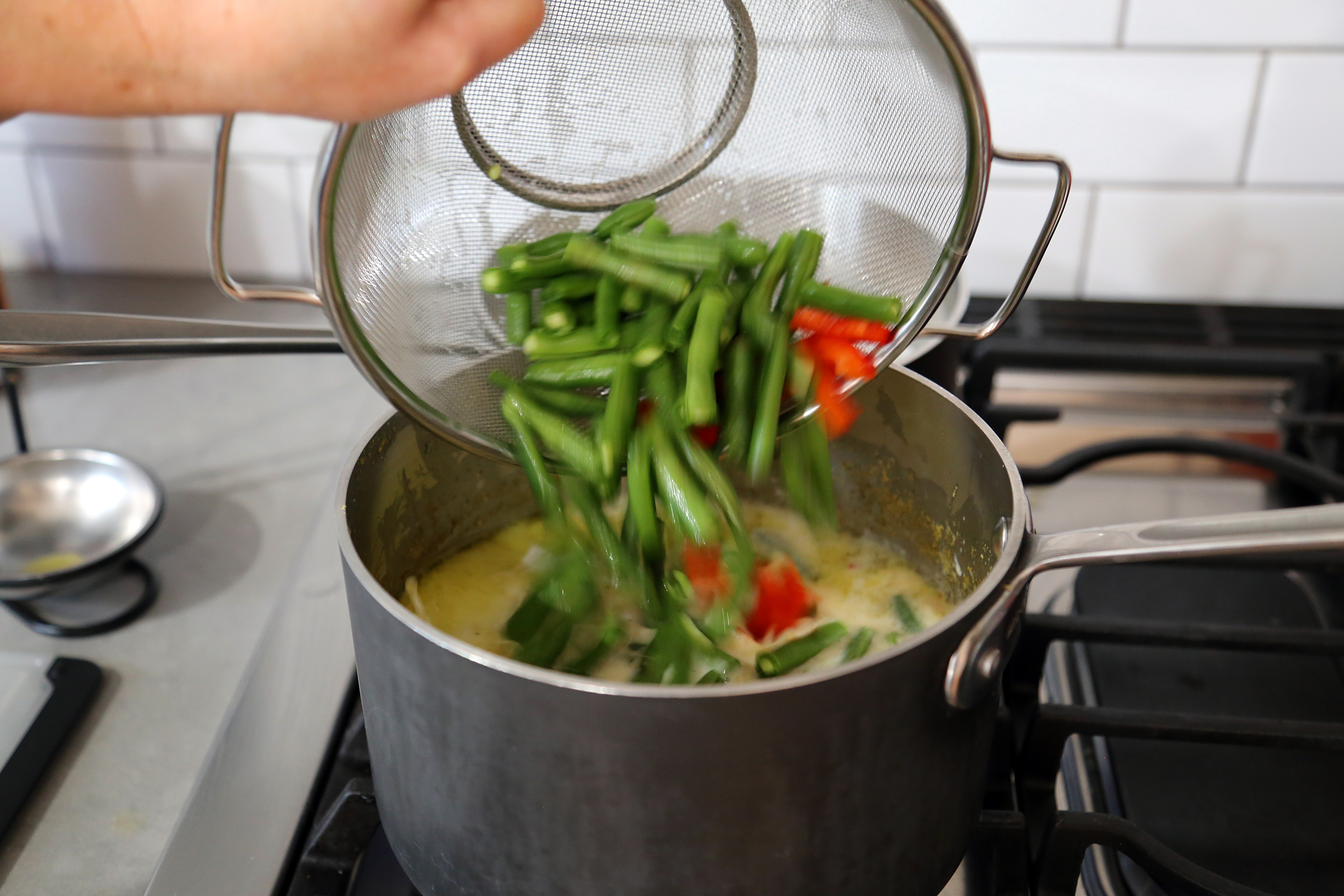 Add the coconut milk, green beans, bell pepper, and green onions to the saucepan.