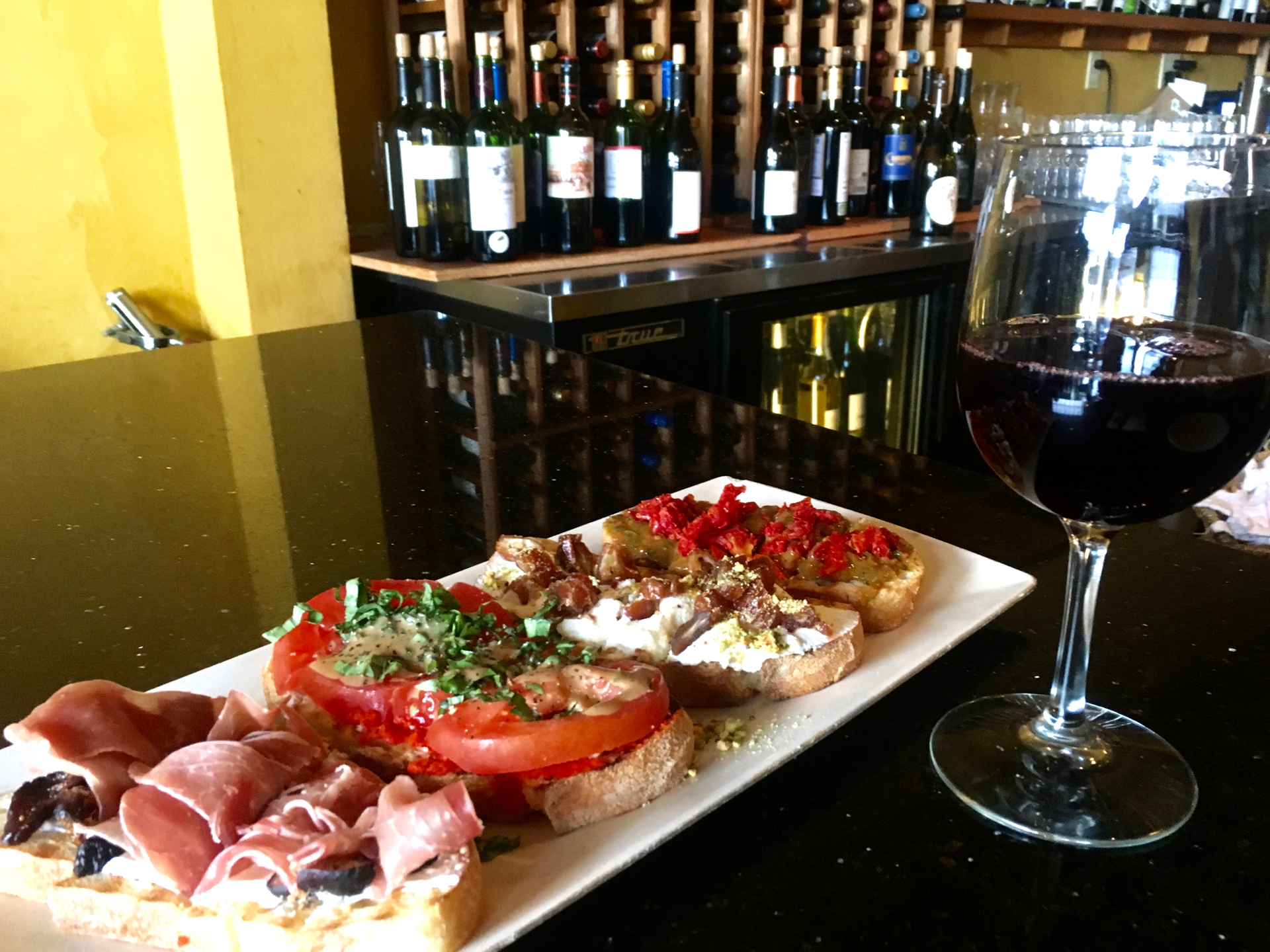 A glass of pinot noir and a selection of savory and sweet bruschetta at B Street & Vine.