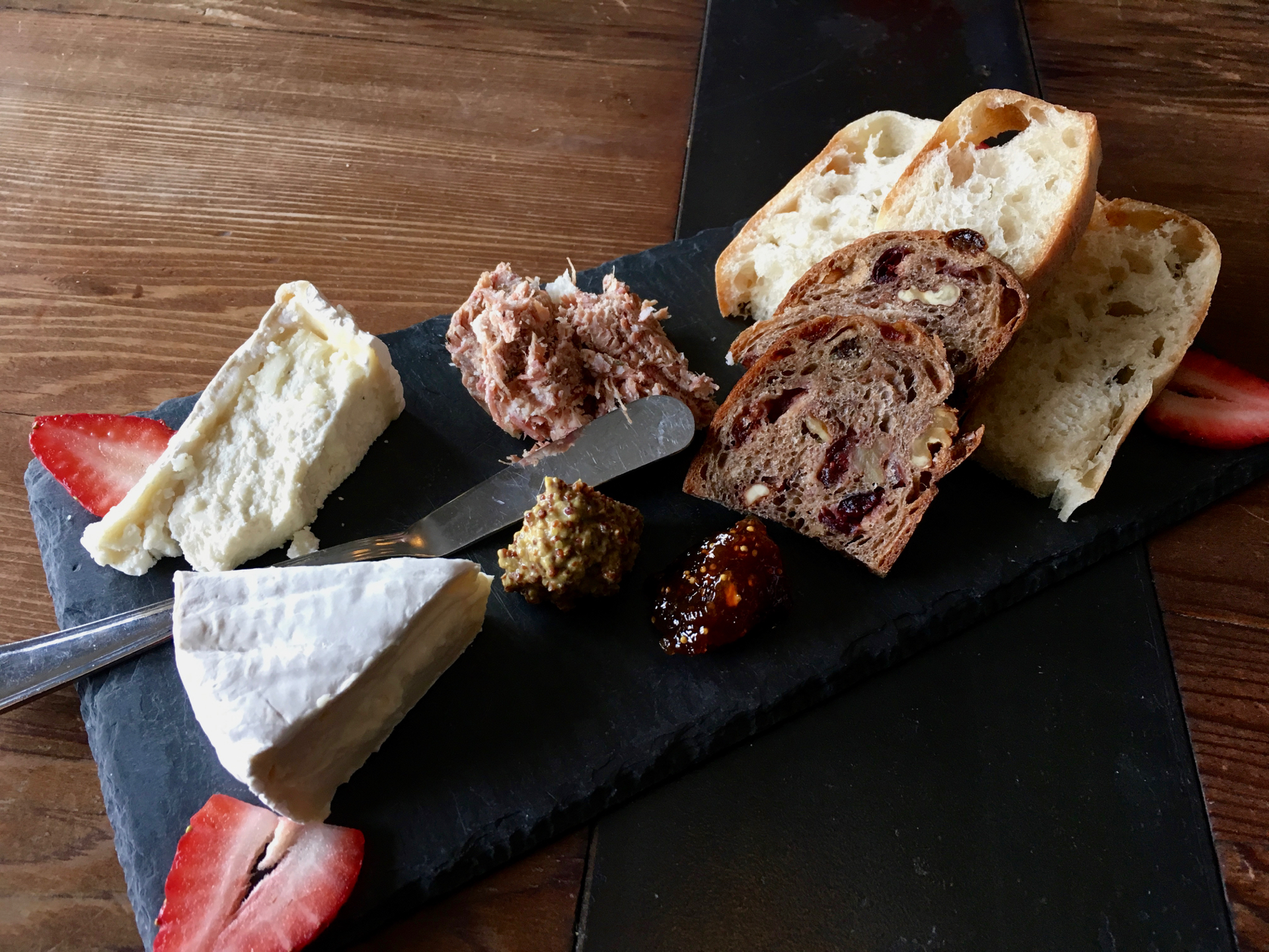 A cheeseboard at Rootstock Wine Bar with Marin French triple cream brie, Cypress Grove truffle tremor, pork rillette and Acme bread.