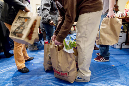Volunteers gather bags of groceries for people seeking assistance at a food pantry in Concord, Mass. Many groups that help low-income families get food aid say they've seen an alarming drop recently in the number of immigrants applying for help.