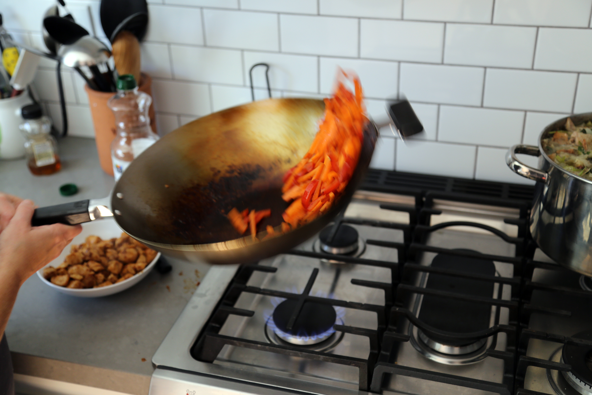 Add a teaspoon or two of oil to the wok, then add the bell pepper and carrots. Cook, stirring, for about 5 minutes, until just starting to become tender.