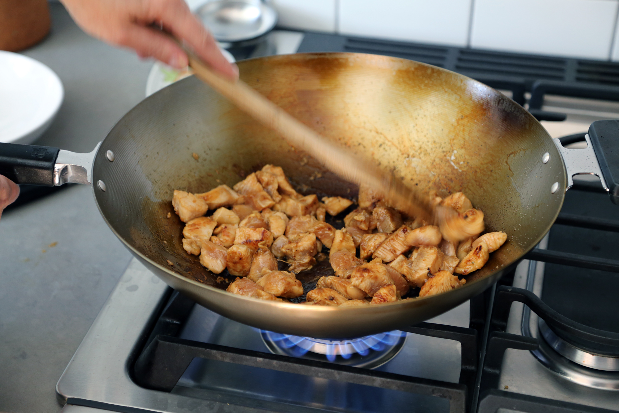 When the oil is very hot, add the chicken. Cook on the first side without moving it, until it begins to brown, about 2 minutes.