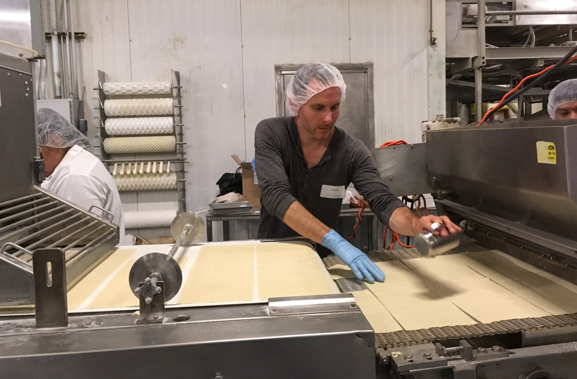 Kevin Rodriguez salts the matzo by hand. He later invested $8,000 in an antiquated salting machine to help with the process.