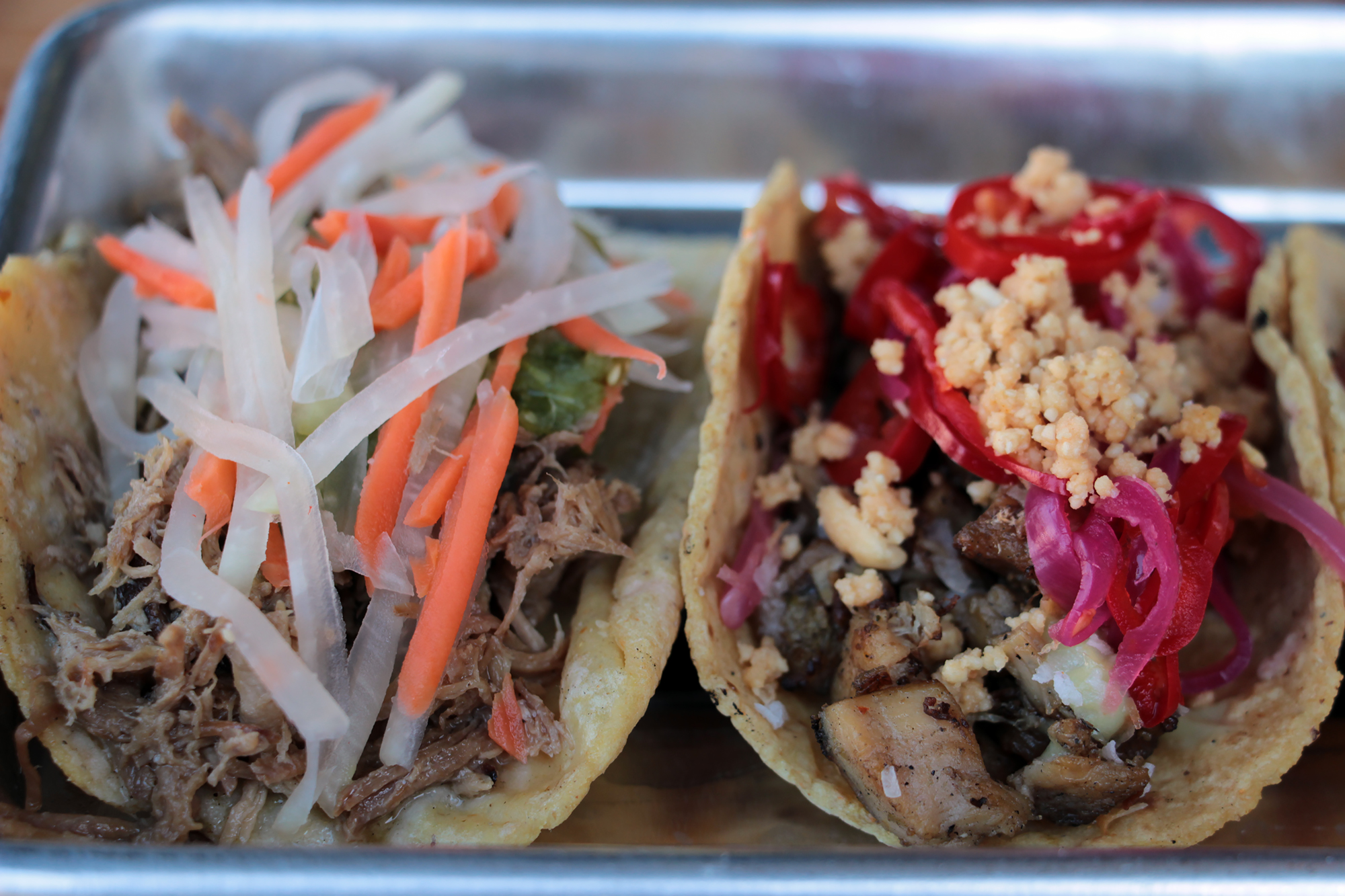 Filipino Pork Adobo (L) and Khmer Lemongrass Chicken tacos.