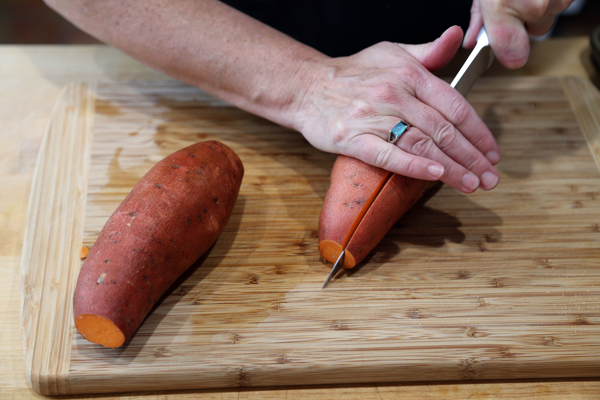 Scrub the sweet potatoes clean, then cut lengthwise in half.
