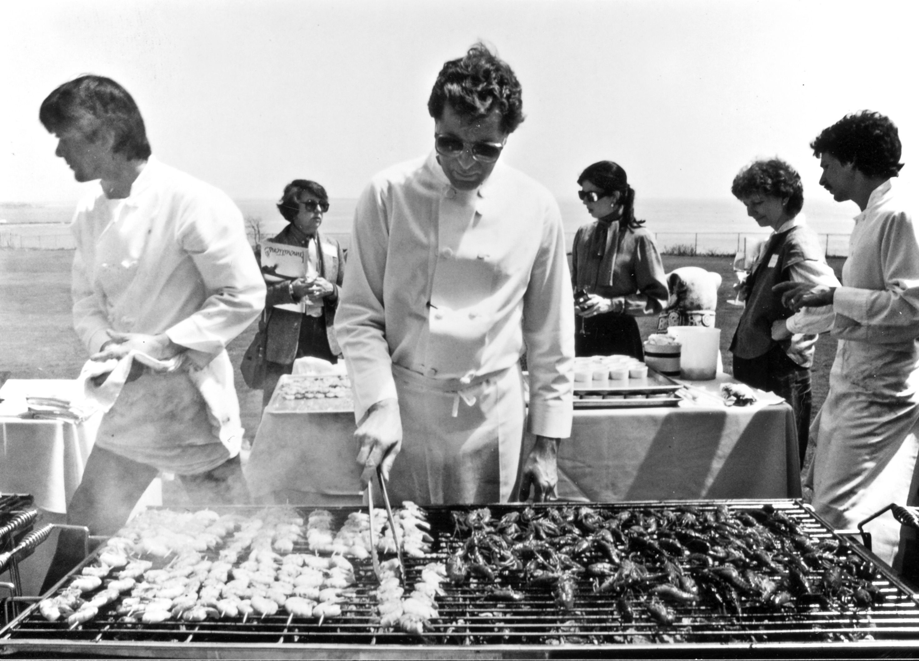 "Jeremiah Tower grills lunch for 100 food journalists on the lawn of the Astor mansion in Newport Beach, R.I., in 1983. Tower wowed the East Coasters with his ""new California"" or new American cooking."