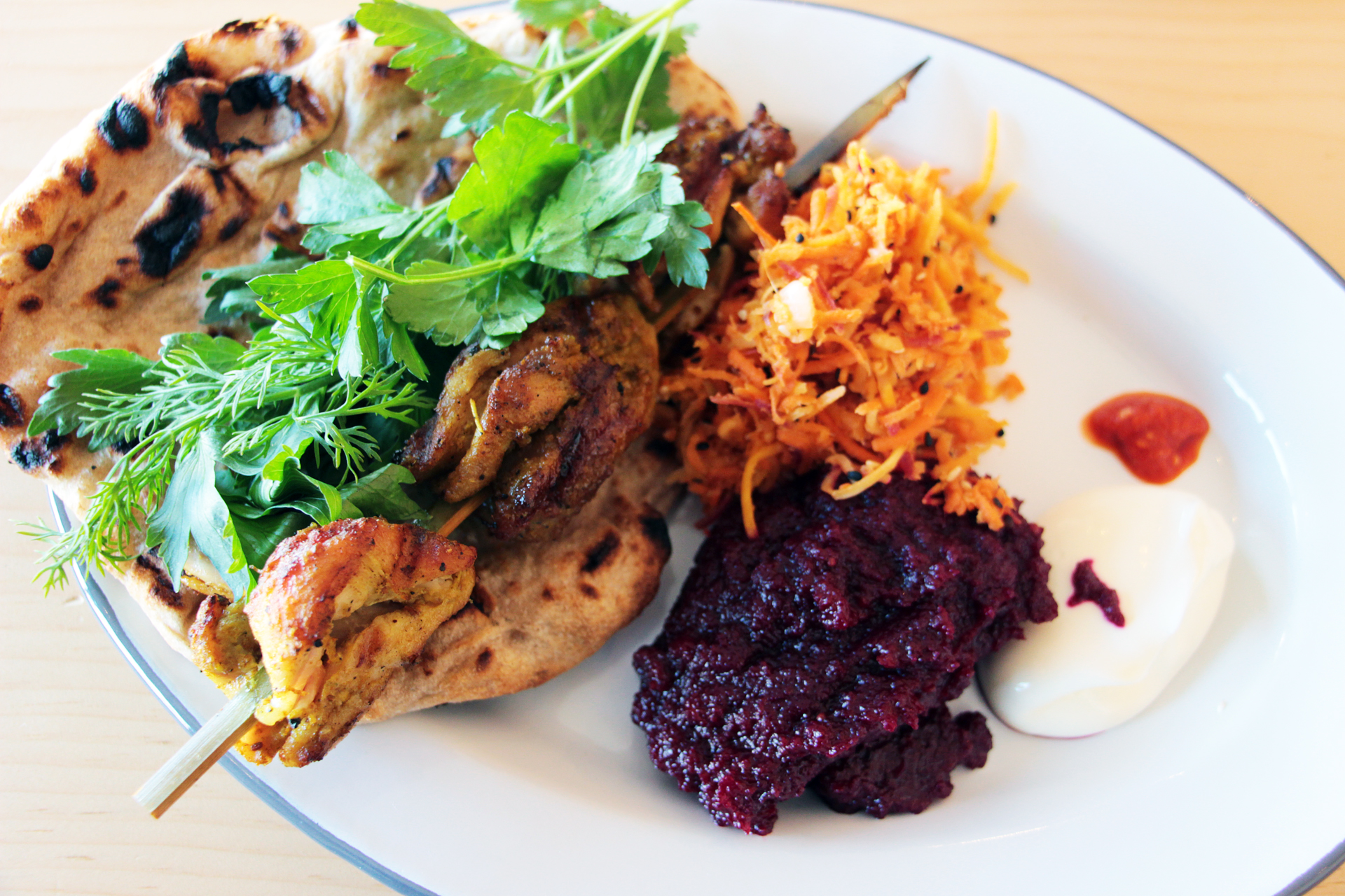 Chicken Kebab Plate, in a marinade of turmeric and other spices, grilled skin-on and served with flatbread, a raw carrot salad with caraway and mustard seeds and mashed beets.