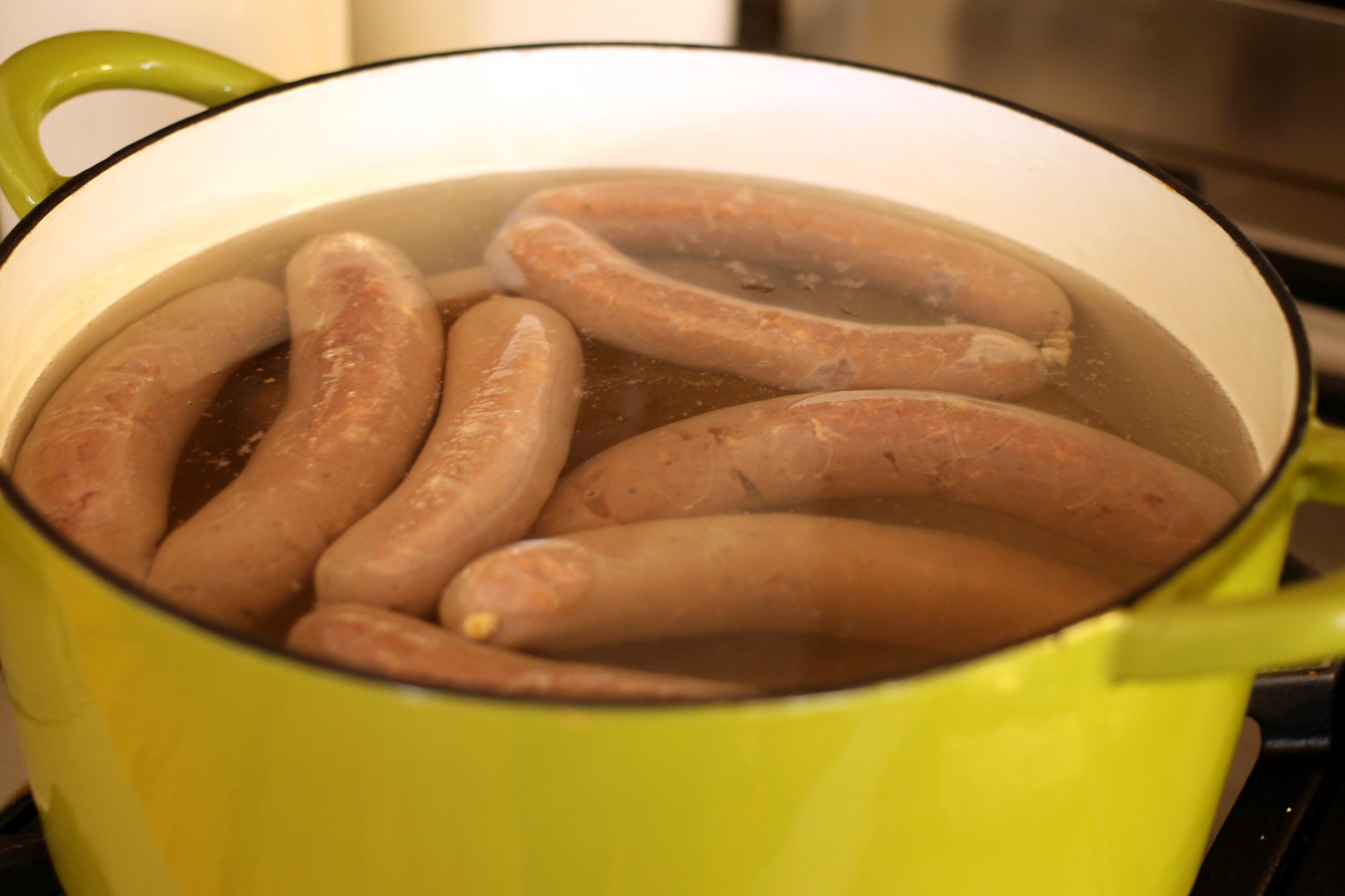 Cooking the sausages gently in water will keep the skins from getting wrinkled when you finish them on the grill or stovetop.