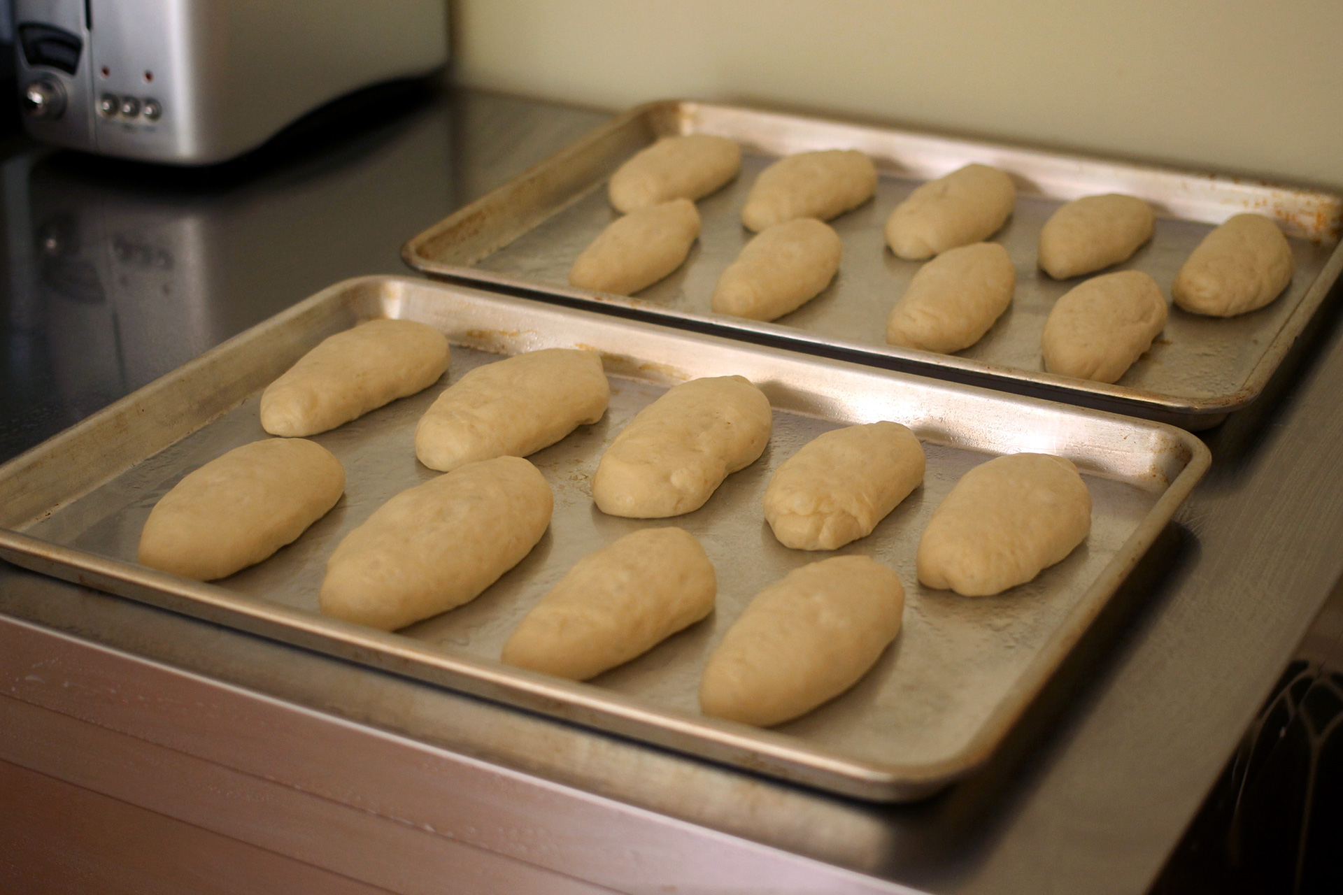 After rolling the balls into cylinders, place them on parchment-lined baking sheets — not greased sheets as you see above. (The buns will stick!)