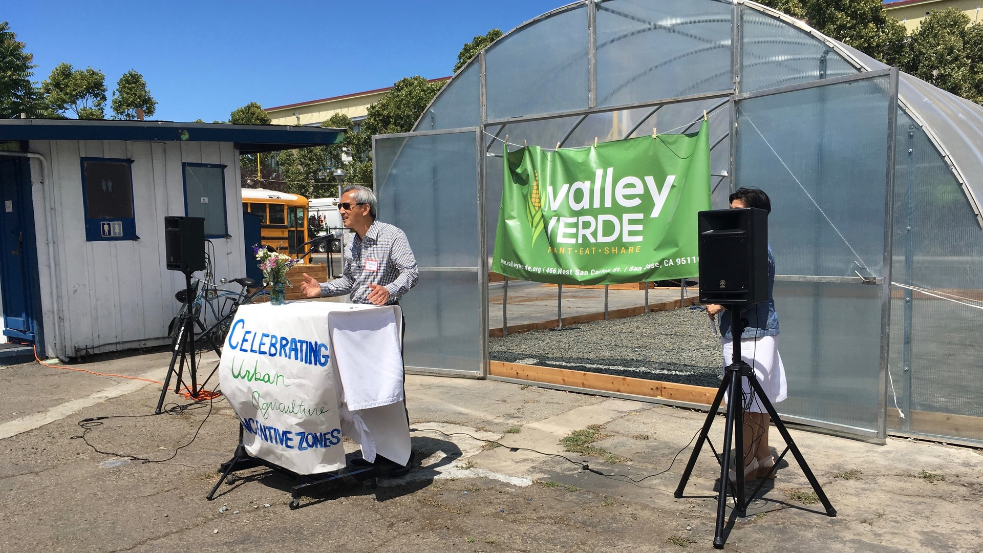 "Phang Do addresses a crowd that gathered for the grand opening of the greenhouse on his property. He plans to develop after five years but is happy to let Valley Verde have the run of the place before then. Do says ""At a time when national politics is so divisive, nice to see local community come together."""