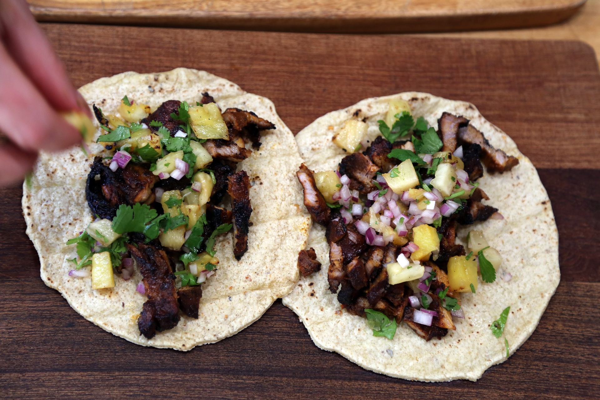 To assemble the tacos, heap some pork al pastor onto a tortilla, top with the pineapple mixture.