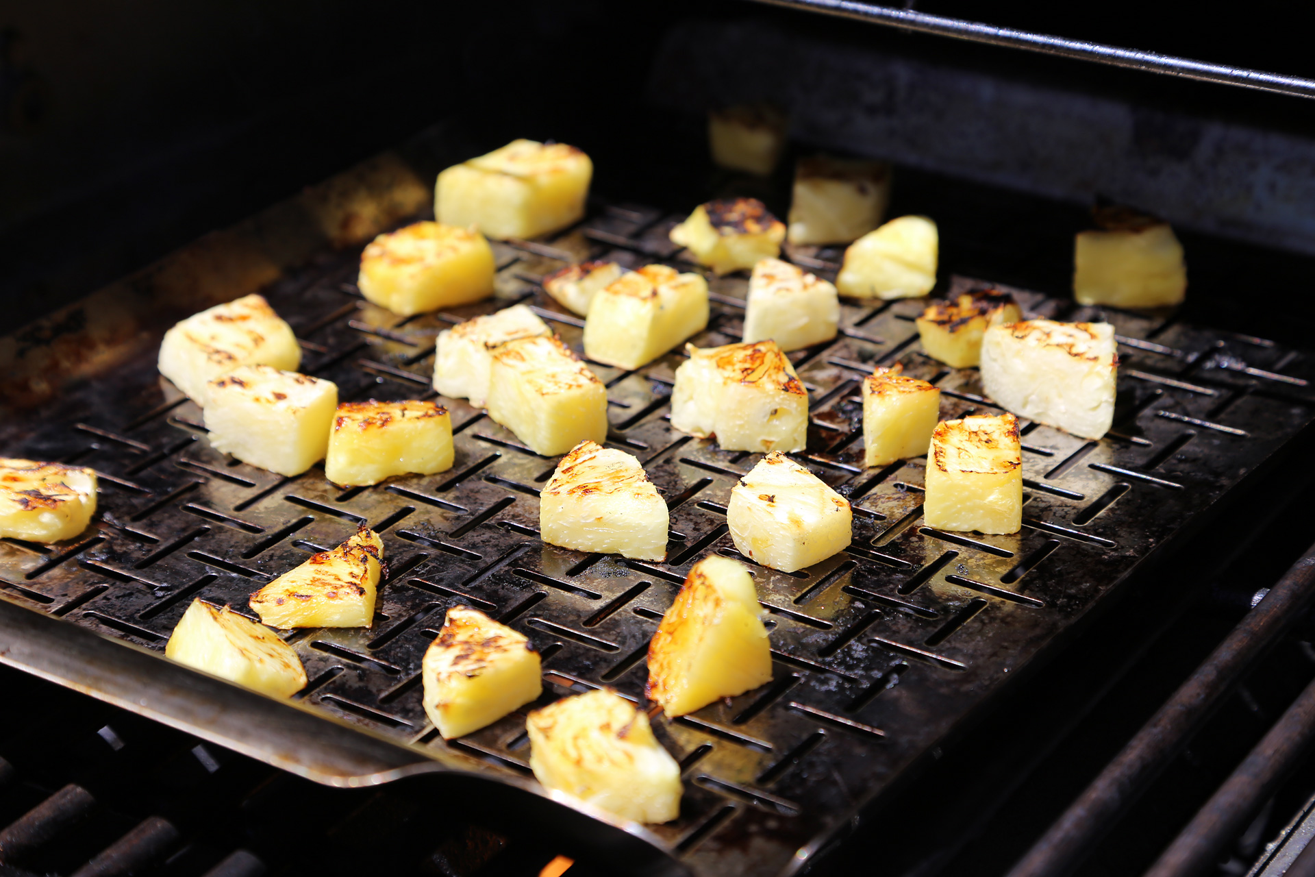 Using a perforated grill pan, grill the pineapple over direct heat until charred, about 7 minutes.