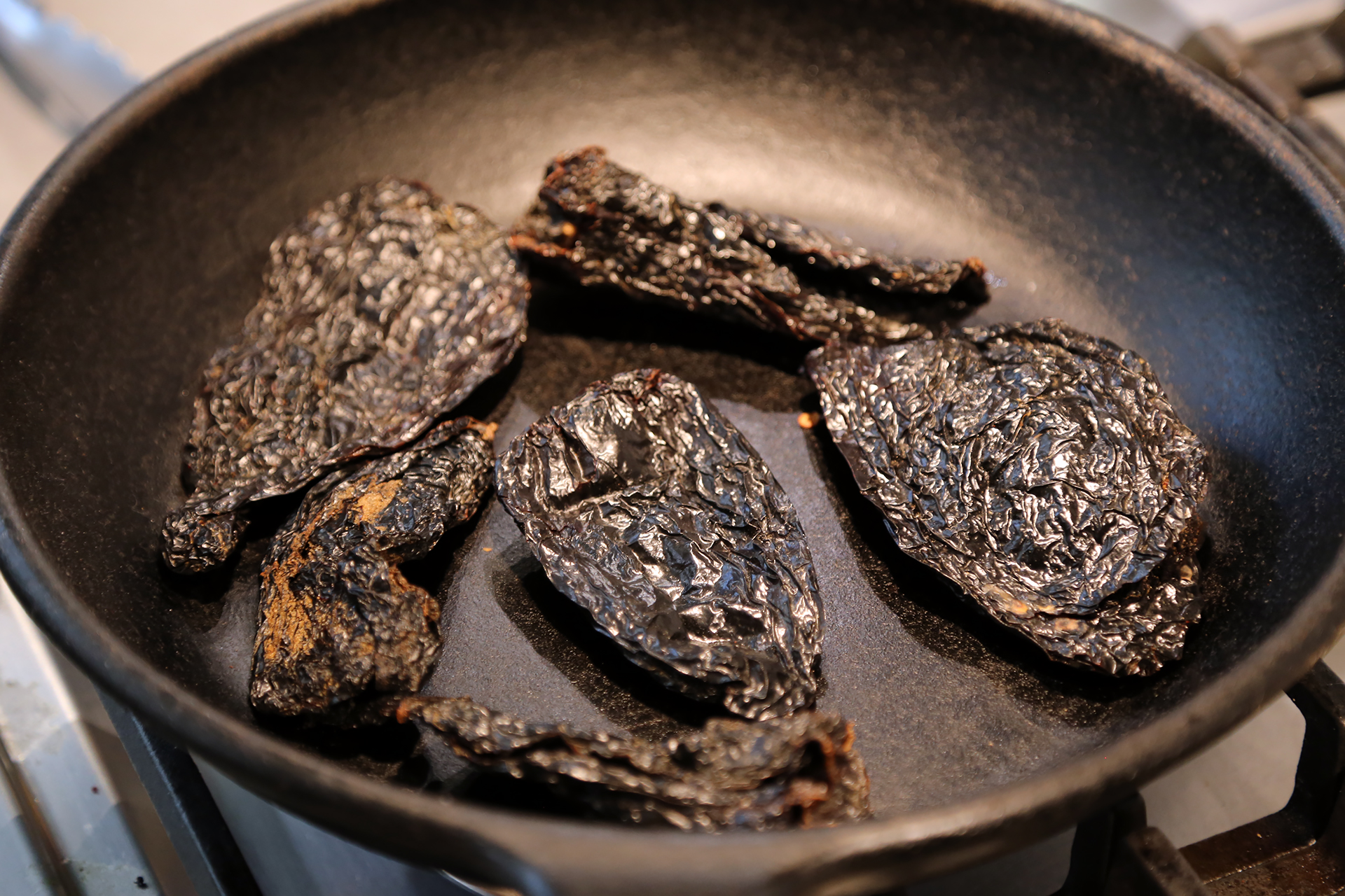 In a large skillet (with a lid) over medium heat, toast the chiles until fragrant and toasted, turning often, about 5 minutes.
