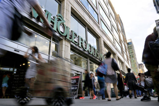 Pedestrians pass in front of a Whole Foods Market store in Union Square, in New York, in 2015.