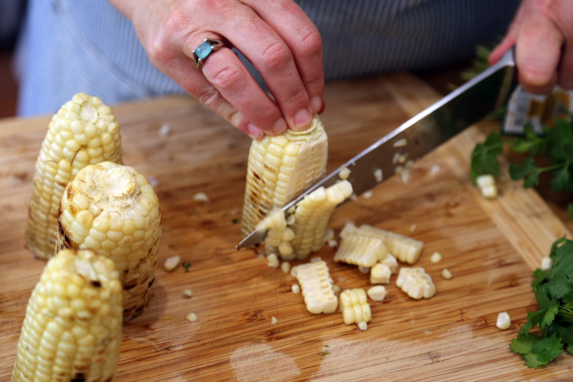 Transfer to a cutting board. Cut the kernels from the corn and place in a shallow serving bowl.