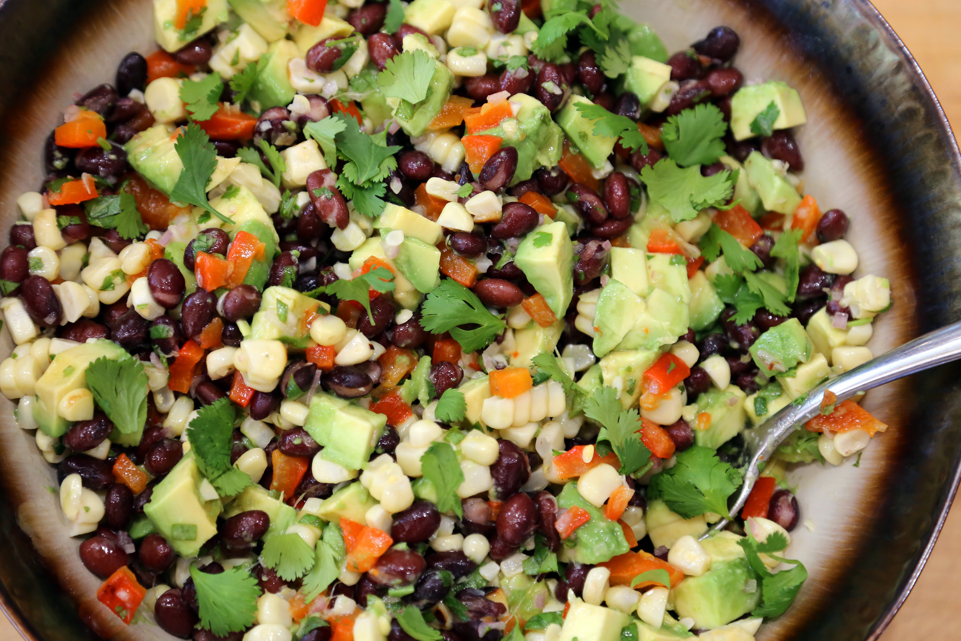 Garnish with more cilantro and serve the Grilled Corn, Red Pepper, Black Bean and Avocado Salad with Cilantro Vinaigrette