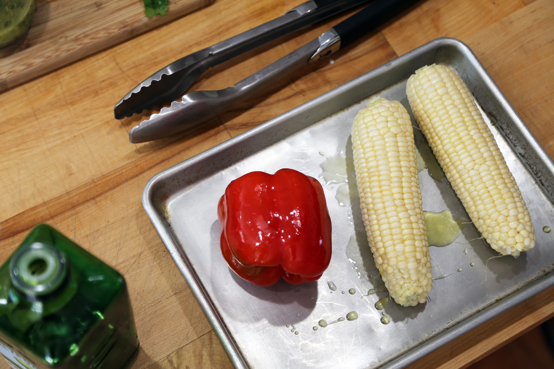Coat the corn and pepper in olive oil.