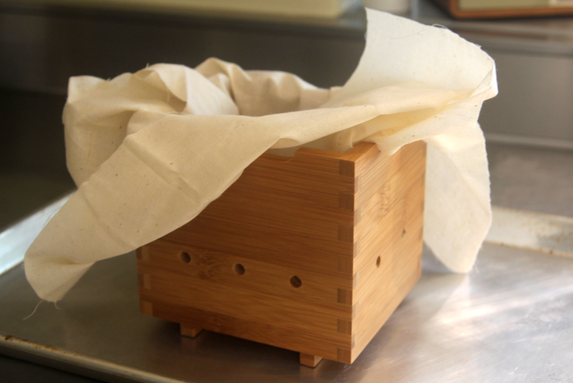 A wooden tofu mold with butter muslin.