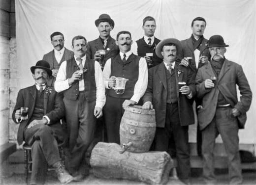 A group of men with full glasses proudly pose with their keg of beer, San Francisco, California, 1895.