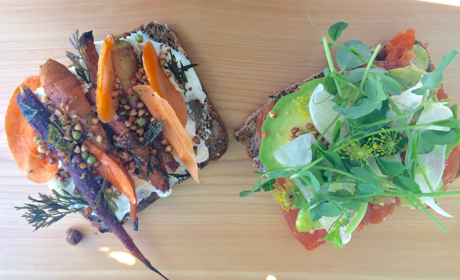 (L) Roasted pomegranate-cured carrots, toasted buckwheat,  tahini and lebna, crispy carrot greens and (R) salmon, avocado, icicle radishes, micro greens, dill honey mustard, flowering fennel. Both smørrebrød sandwiches created by Kristen Rasmussen on her homemade rye bread. Anna Mindess