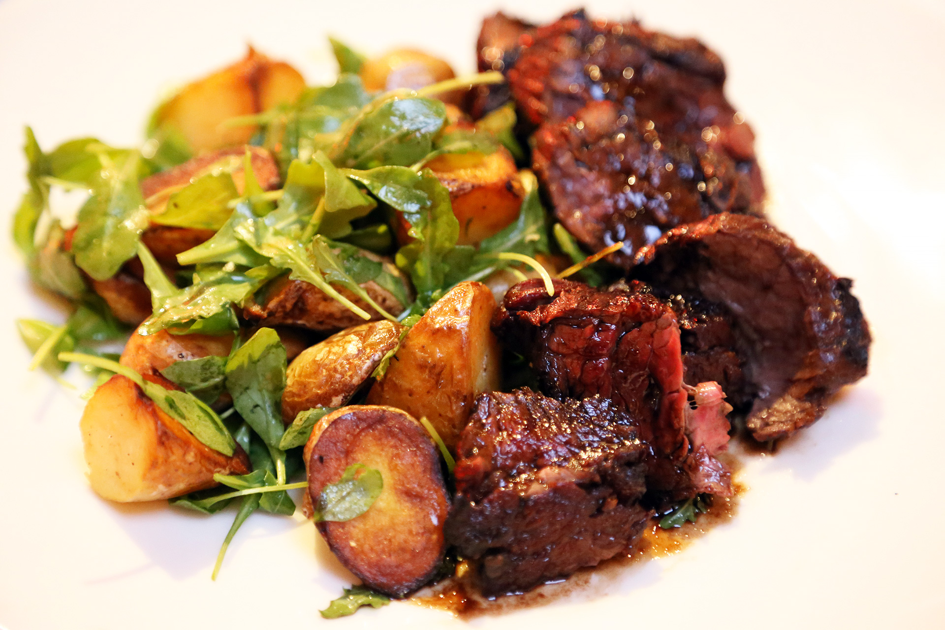 Medium-rare hanger steak with fingerling potatoes and a baby arugula salad.