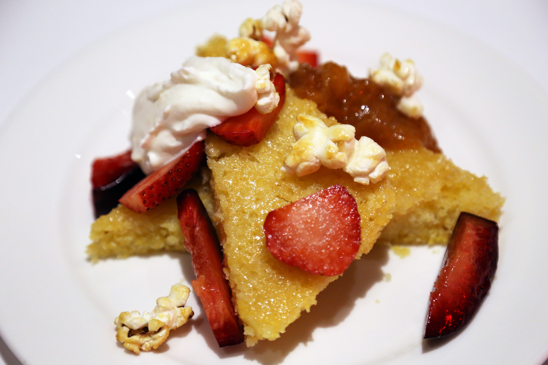 Polenta cake topped with ricotta cream, summer fruit, and a surprising and wonderful garnish of kettle corn.
