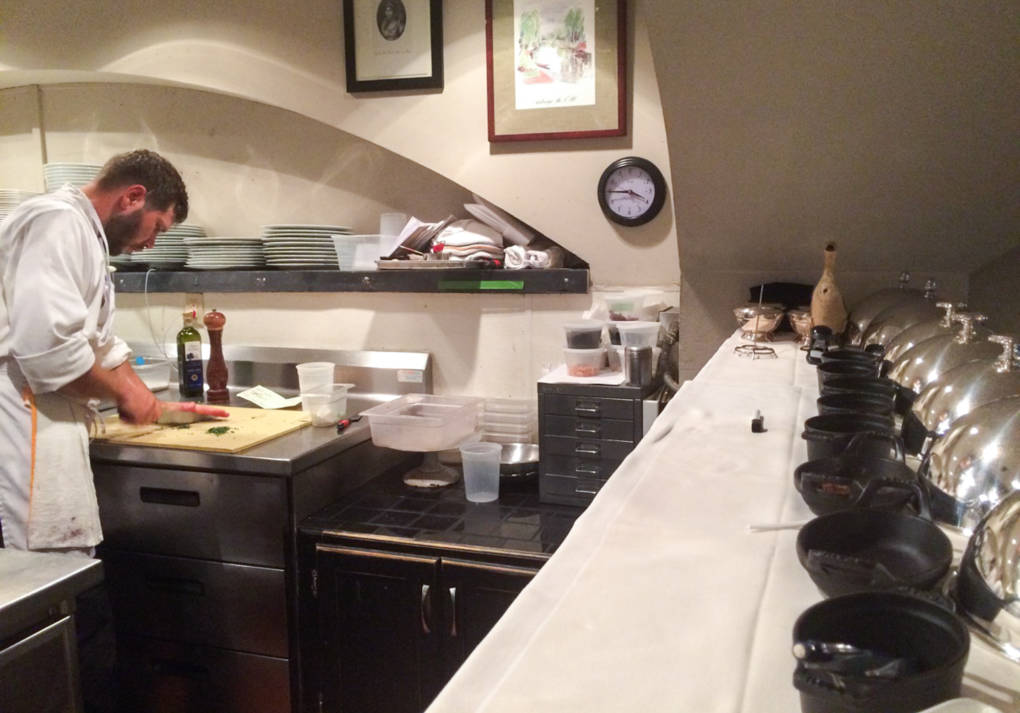 David Uzzell at work in the kitchen at Marcel's. Uzzell has a written list of daily tasks from chef and owner Robert Wiedmaier at his station, and his ever-present notepad and pencil on the shelf above serves as communication tools for more specific instructions.