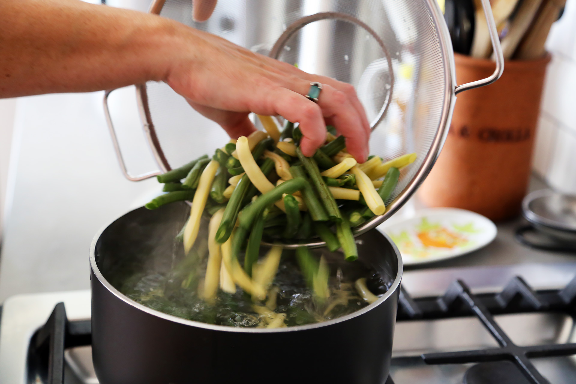 Bring a saucepan half filled with salted water to a boil over high heat. Reduce the heat to medium and add the green beans.