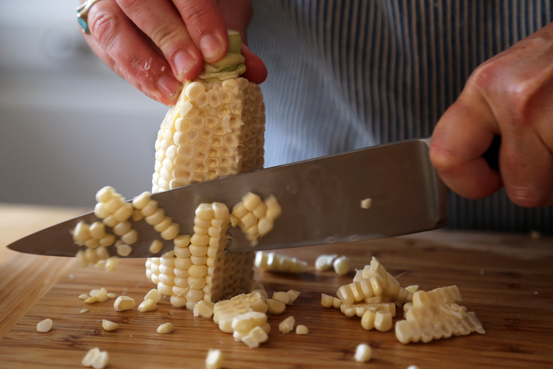 Stand the cob on the flat end, and, using a sharp knife, cut down the side of the cob to remove the kernels.