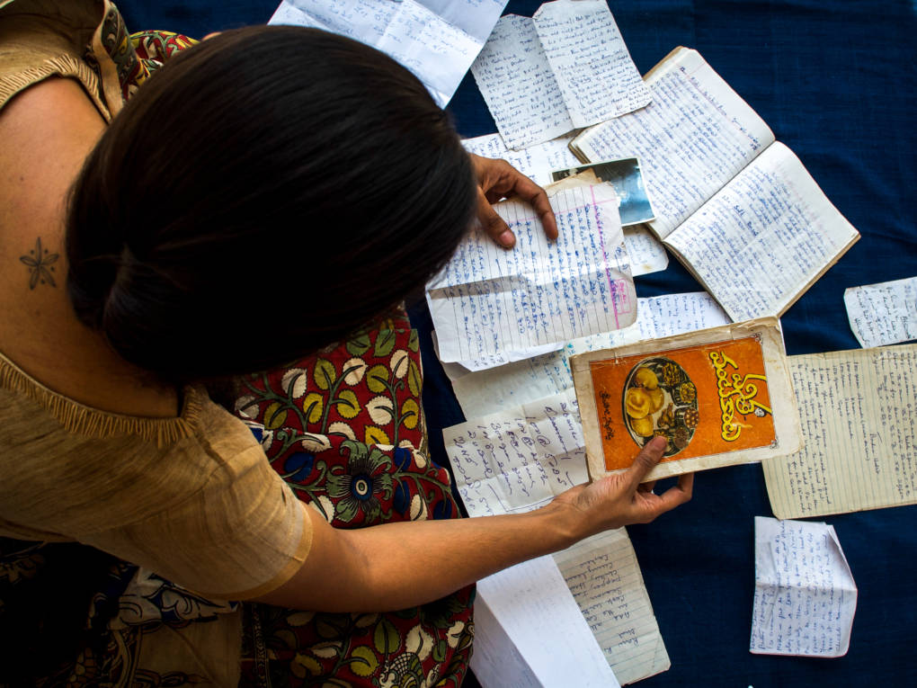 """Archana Pidathala sorts through old recipes that belonged to her grandmother. """"She never once complained or felt overwhelmed by the incredible amount of cooking she did for us,"""" she says."""