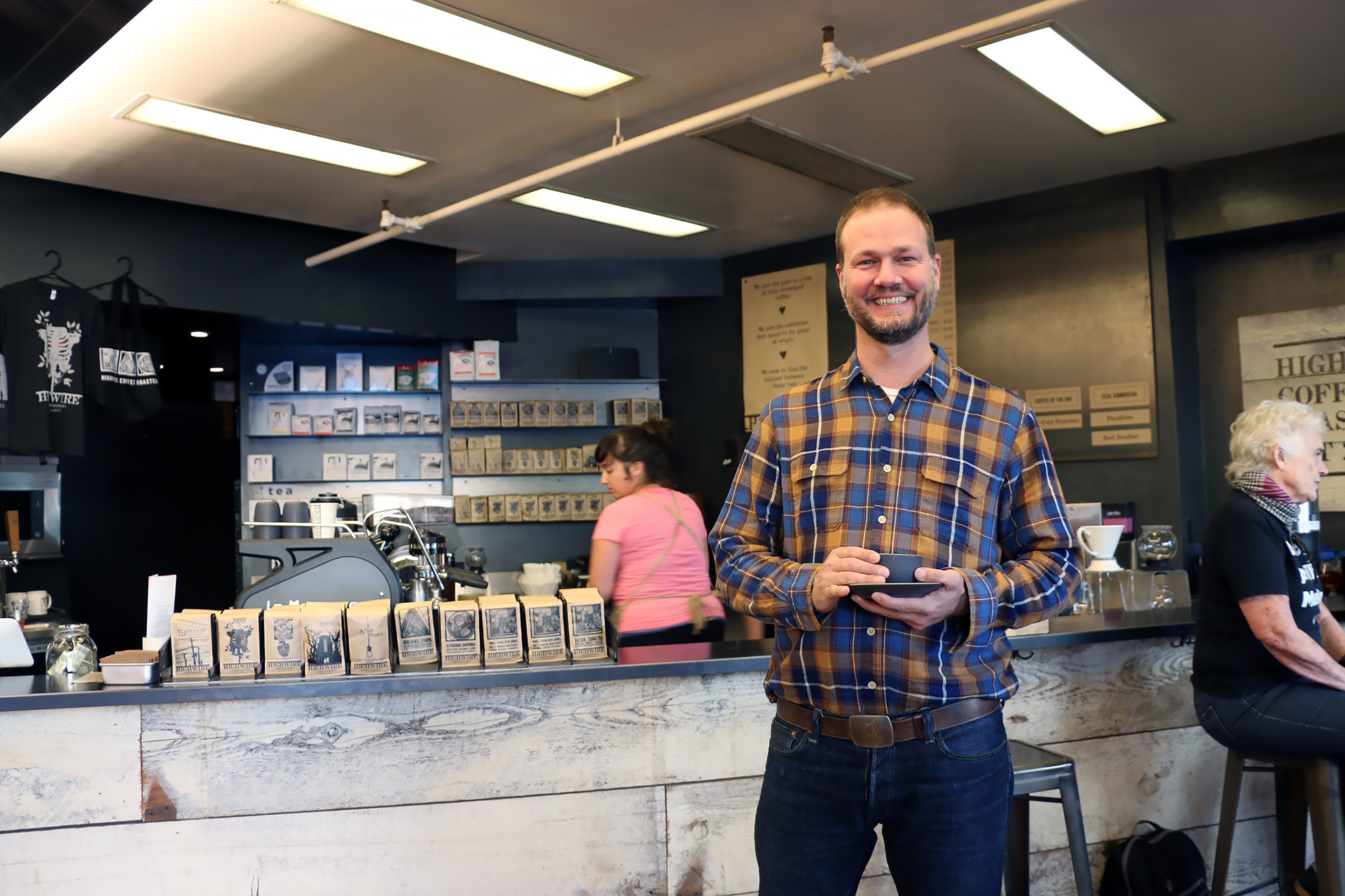 Highwire co-owner Robert Myers enjoys a cup in front of his café's current selections.