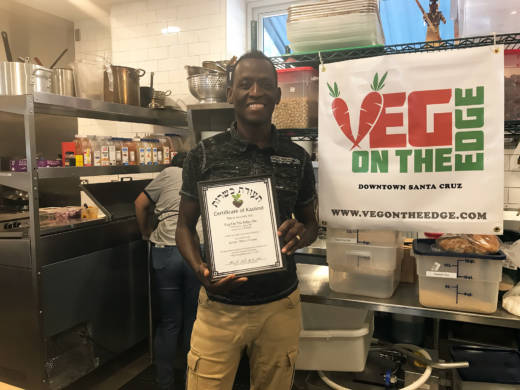 Akindele Bankole, owner of Veg on the Edge with his kosher certificate.
