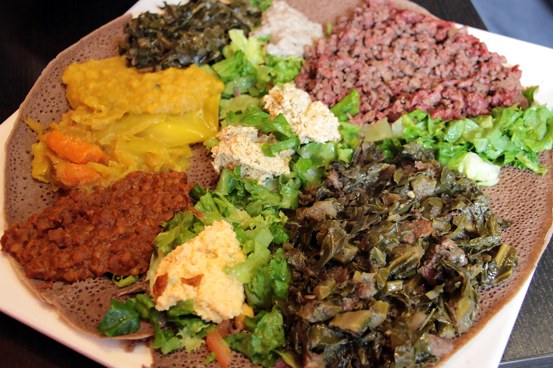 Combo platter: Vegetable dishes and Kitfo.