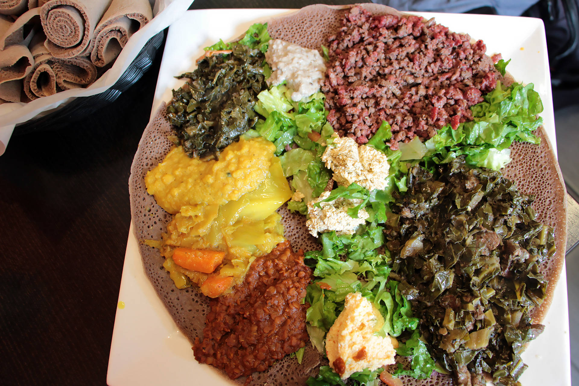 A combo platter with vegetable dishes and kitfo at Tadu Ethiopian Kitchen in SF. Wendy Goodfriend