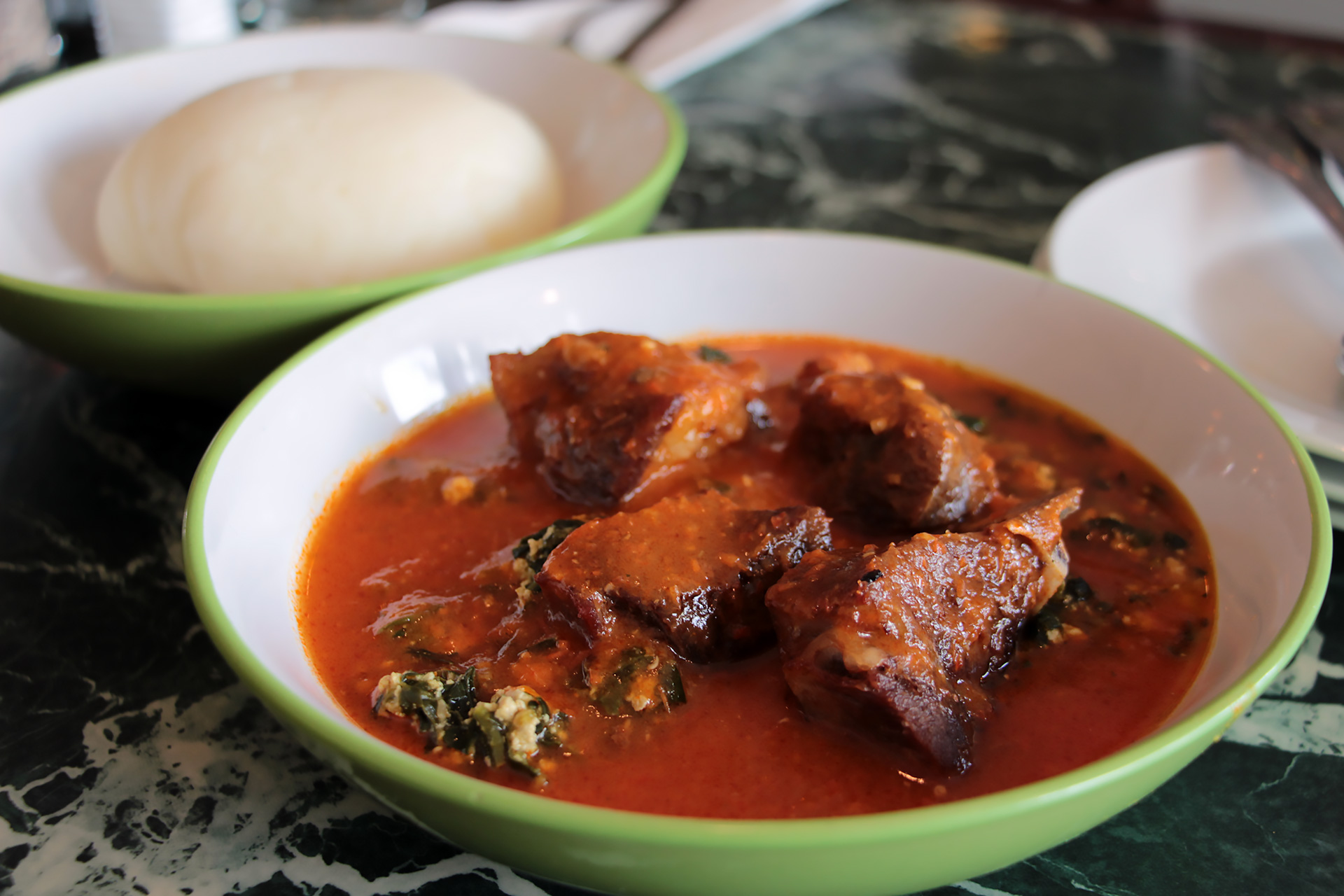 Goat served on the bone in the rustic, chunky tomato and spinach stew with mashed egusi. Served with Fufu.