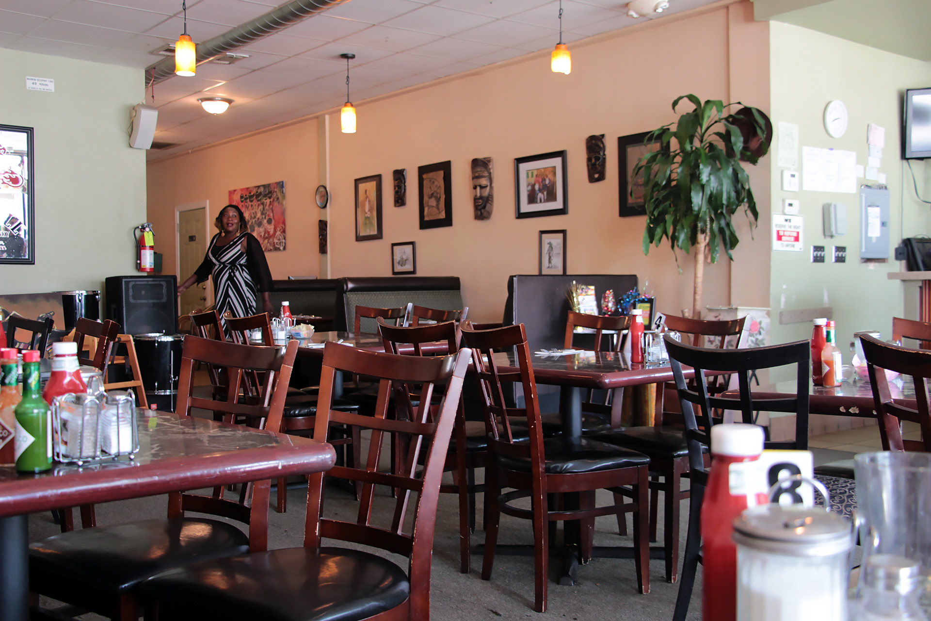 Miliki interior dining area with host Enny Aregbe in background.